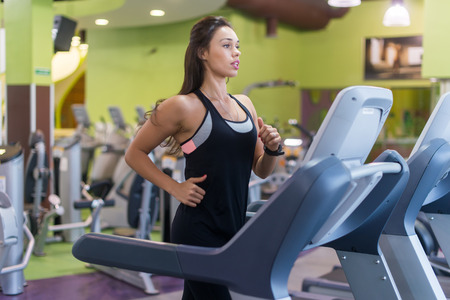 self conscious: Fit women doing cardio exercises, running on treadmills in the gym Stock Photo