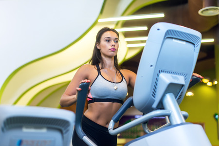 Fit woman exercising at fitness gym aerobics elliptical walker trainer workout Stock Photo