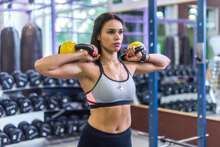 kettles: Mujer que hace ejercicio con pesas rusas en el gimnasio