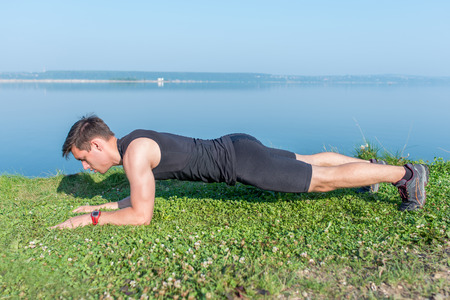 back exercise: Fit man doing plank core exercise working on abdominal back muscles.