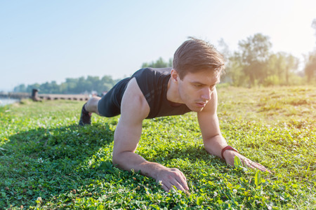 man at work: Athlete doing a plank exercise on a sunny day