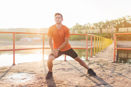 lunges: Fit man warming up doing lunges exercising during morning run