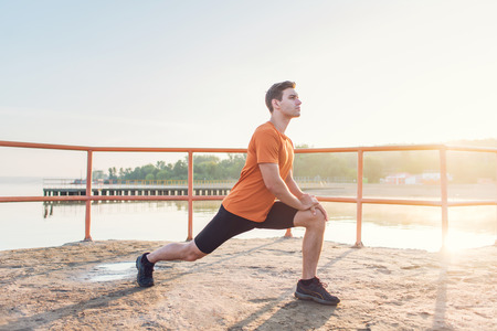 Young fit man stretching legs outdoors doing forward lunge Foto de archivo