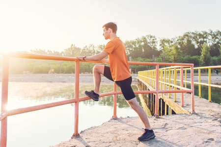 Fitness man stretching his leg muscles outdoors