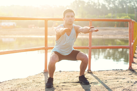 Fit man working out glutes with bodyweight workout doing squat exercises Stock Photo