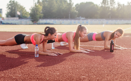 planking: Athletic group of women training on a sunny day doing planking exercise in the stadium Stock Photo