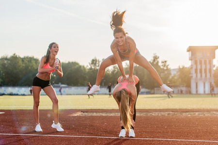 Fit women at the stadium playing leap frog Stock Photo