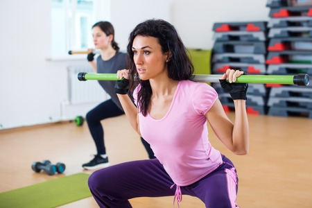 sit up: Group of people excercising with bars in gym doing squatting with a barbell at fitness club. Stock Photo