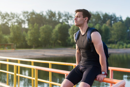recovery: Portrait of fit man runner sitting and resting outdoors near river