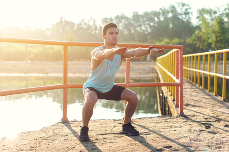 Fit man warming up doing squats stretching arms forward outdoors