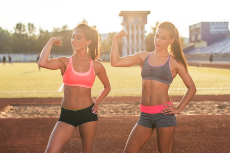 sportwoman: Sporty young women with perfect bodies showing biceps