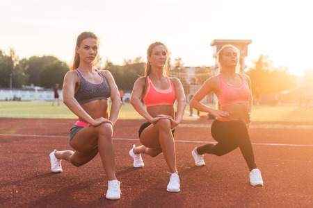 lunge: Young fit women stretching legs outdoors doing forward lunge.