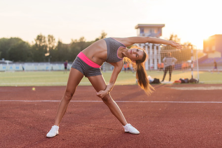 ejercicio aeróbico: Fit woman doing side bend stretching exercise warming up Foto de archivo