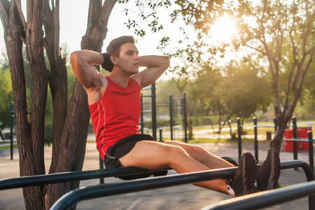 situp: Fit man doing sit ups on parallel bars outdoor fitness station Stock Photo