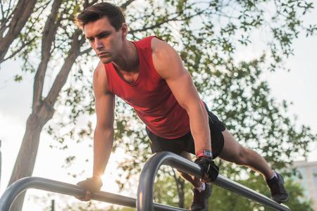 and the horizontal man: Fit young man doing push ups on horizontal bar outdoors. Stock Photo