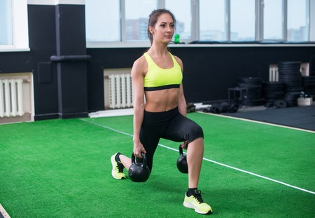 lunges: portrait of a sporty woman doing lunges with dumbbells, working out legs muscles. Stock Photo