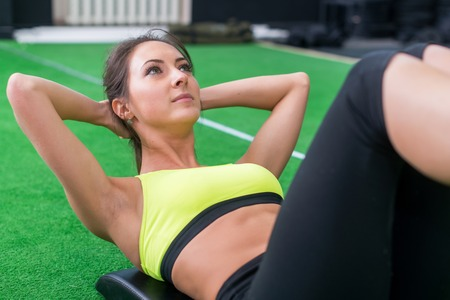 laying abs exercise: portrait of an athletic woman doing exercising abdominals work-out lying in gym. Stock Photo