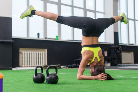 asana: fit woman doing yoga exercise, headstand asana in gym Stock Photo