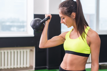 young fit woman doing exercises lifting kettlebell, working out biceps, triceps, back muscles.