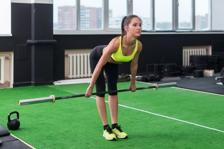 portrait of a fit woman exercising with barbell doing deadlift , working out back muscles and arms.