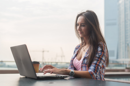 coder: Young woman using a laptop working outdoors. Female looking at the screen and typing on keyboard.
