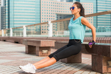 tricep: Fit woman doing triceps bench dips exercise while listening to music in headphones. Fitness girl working out in the city.