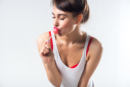 lollypop: Young brunette model with lollipop posing studio shot on white background, not isolated.