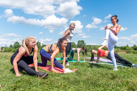 arms up: Group women warming up before training stretching, exercising outdoors