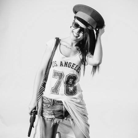 Fashion swag sexy girl holding gun woman having fun wearing police cap black and white.