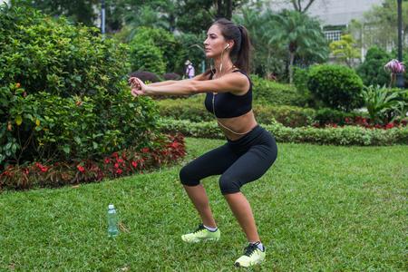 en cuclillas: Atleta de sexo femenino joven que hace ejercicios en cuclillas al aire libre en el parque. niña de ajuste que se resuelve su núcleo y glúteos con el peso corporal Foto de archivo