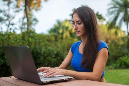 socializando: Estudiante bastante femenina Europea usa su computadora portátil estudia al aire libre. Niña de socialización en su pc en el jardín