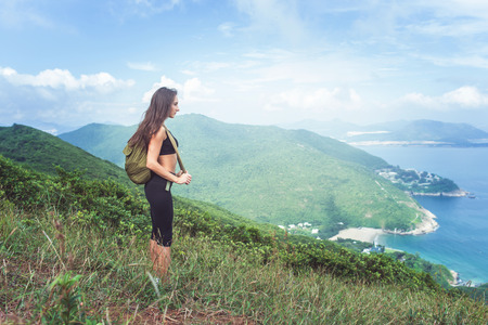 trekker: Backpack female traveler standing on hill looking at sea and mountains. Trail runner taking a break and enjoying view of nature.