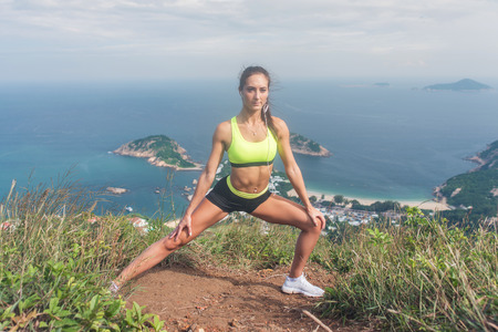 outdoor training: Fitness woman stretching her leg muscles doing side lunge exercise preparing for cardio work-out in mountains by the sea.