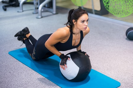 fitball: Fit woman exercising with medicine ball workout out arms Exercise training triceps and biceps doing push ups.