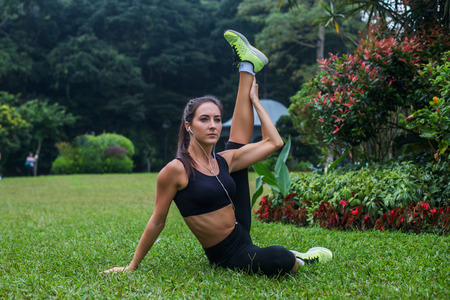 practicing: Sporty flexible young woman doing hamstrings stretching exercises on grass outdoors. Active fit girl training in park. Stock Photo