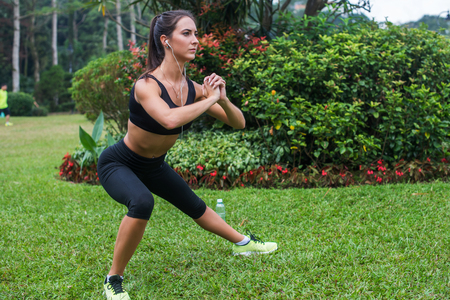 Pretty young fit woman doing stretching exercises in park. Fitness woman doing side lunges outdoors Stock Photo