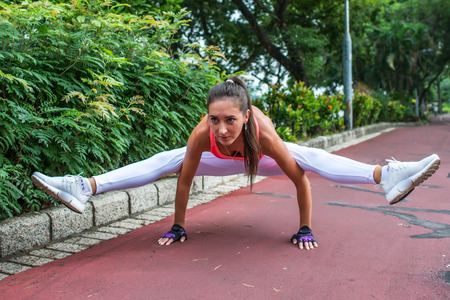Sporty fit young woman doing handstand exercise in firefly posture. Female athlete working out in the park Stock Photo