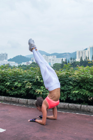Sportswoman doing handstand yoga exercise standing on her forearms with straight legs on path in the park with view of city buildings.