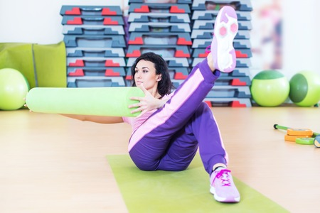 russian: Fit woman doing abs workout exercise russian twists with raised leg. Stock Photo