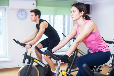 cardio workout: Group training people biking in the gym, exercising legs doing cardio workout cycling bikes. Stock Photo