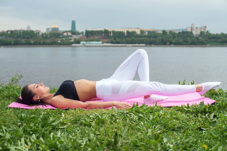laying abs exercise: Fit woman practice exercise outdoors street training Stock Photo