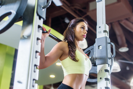 cross bar: Fit woman doing shoulder press exercise with a weight bar Smith machine at gym