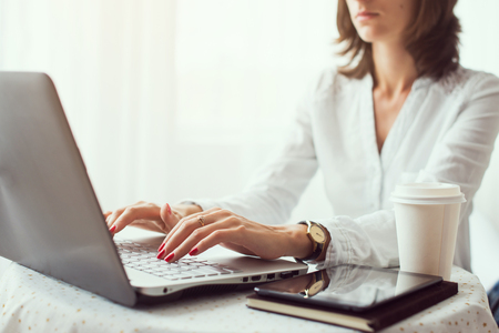 Woman freelancer, student or blogger typing on computer sitting at wooden table home office