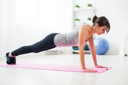 自宅練習のマットに彼女のリビング ルームの床で腕立て伏せをやって女性に合う 写真素材