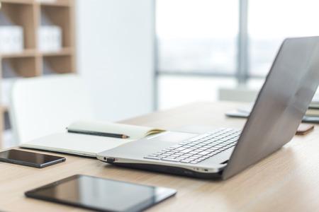 Lugar de trabajo con ordenador portátil portátil mesa de trabajo cómodo en la oficina con ventanas y vistas a la ciudad Foto de archivo