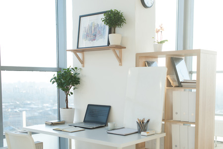 Side view picture of studio workplace with blank notebook, laptop. Designer comfortable work table, home office Standard-Bild