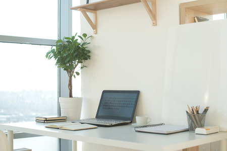 Side view picture of studio workplace with blank notebook, laptop. Designer comfortable work table, home office Stockfoto