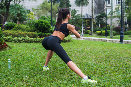 lunge: Back view of fit girl doing side lunge exercises outdoors