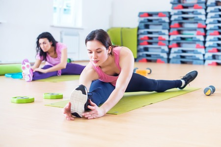 abductor: Woman doing cross split exercise working out her hip abductor muscles and ligaments. Fit female athlete stretching splits in gym. Stock Photo