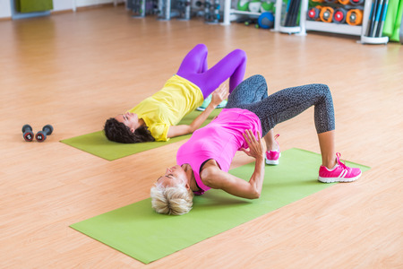 Women training their glutes by doing bridging exercise on mats in gymnasium